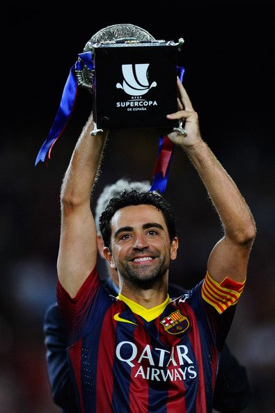 Xavi Hernandez of FC Barcelona holds up the trophy after winning the Spanish Super Cup during the Spanish Super Cup second leg match between FC Barcelona and Atletico de Madrid at Nou Camp on August 28, 2013 in Barcelona, Catalonia.