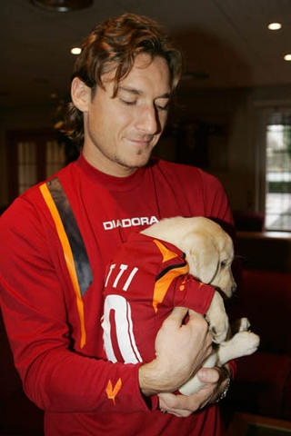 Francesco Totti with a puppy.