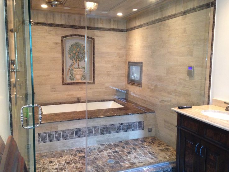 Big bathtub behind glass doors with enclosed shower - built-in tv in the tile wall.