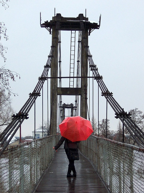 red umbrella on a bridge. Photo by Ell22