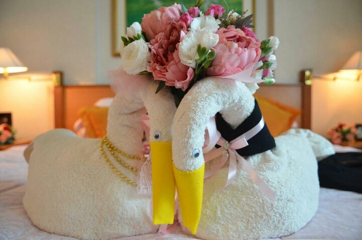 Peony and rannunculus wedding bouquet and a pair of handmade faux swans made of towel.