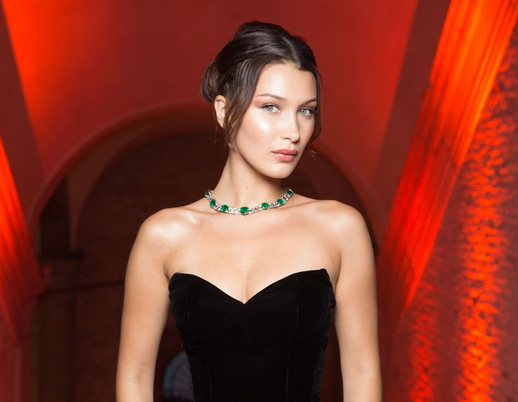 Bella Hadid seen wearing platinum, emerald and diamond Le Magnifiche Creazioni necklace at Bulgari Festa event in Venice, Italy, June 2017. Bella wears a floor length sweetheart neck black dress with a long lace train. To see more Bulgari style: http://www.thejewelleryeditor.com/brands/bulgari/