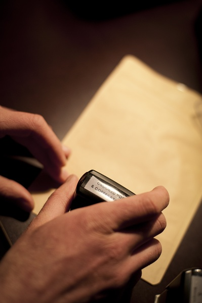 Natural kraft foil stand up pouches are stamped by hand.