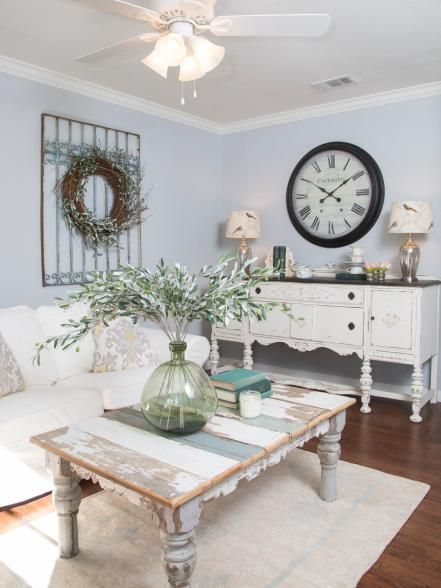 Fixer Upper host Joanna Gaines staged the newly painted living room with bright and feminine yet rustic furniture and accessories, making the room feel cozy with shabby chic style. A wreath mounted on a piece of decorative iron fencing becomes a focal point in the room.