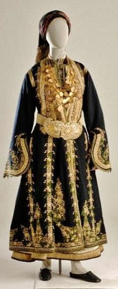 This bridal/festive costume from Argyrokastro/Gjirokastër (southern Albania) with minor variations in the headdress, was worn by both Greek and Muslim women alike. It consists of a long white chemise, short waistcoat, long black overcoat embroidered in gold, and a gold belt and buckle. The breast is covered by the armatha, a chain ornament with gold-plated coins, which was worn for the wedding and then became a family heirloom. The head is covered with a silk gold embroidered headscarf.