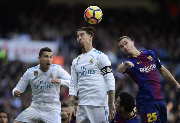 """(FromL) Real Madrid's Portuguese forward Cristiano Ronaldo, Real Madrid's Spanish defender Sergio Ramos and Barcelona's Belgian defender Thomas Vermaelen jump for the ball during the Spanish League """"Clasico"""" football match Real Madrid CF vs FC Barcelona at the Santiago Bernabeu stadium in Madrid on December 23, 2017.  / AFP PHOTO / JAVIER SORIANO"""