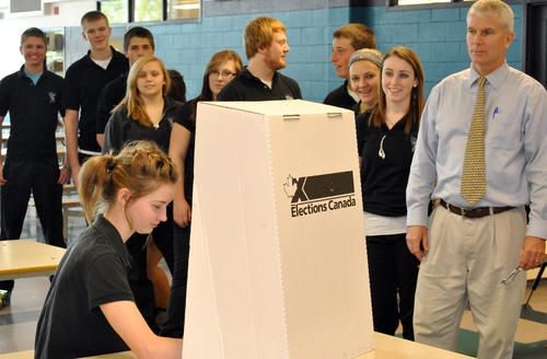 St. Christopher Catholic Secondary School student Alicia Cable casts her vote as the rest of her classroom and teacher Blake Morrison look on.