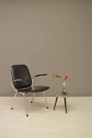 Fana stoel, zwarte skai bekleding en chromen frame. Verkeert in een prima vintage staat. Paul Schuitema (een van de belangrijkste vertegenwoordigers van de progressieve Rotterdamse kunstbeweging in de jaren '20) richtte in 1935 samen met Jan van Ettinger en fabrikant Dekke het meubelmerk en productiebedrijf 'd3 -meubelen' op, dat later overging in Fana Metaal en in de jaren '70 haar deuren sloot.