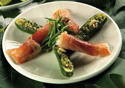 Gli Scampi al prosciutto e zucchine vengono realizzati avvolgendo i frutti di mare con le strisce di prosciutto crudo, quindi svuotando le zucchine e...