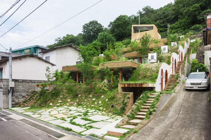 香川県高松市にある、高低差の激しい斜面地を利用した連層長屋を紹介。緑が生い茂り、山の続きに自然と存在している建物は、大地のすみっこに住んでいるかのよう