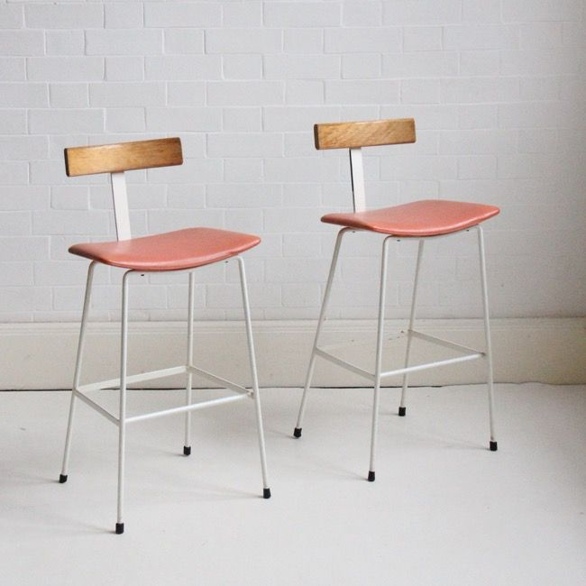 Bar stool designed in the 1950s by Frank Guille for Kandya.  Original condition with powder coated steel rod frame, solid beech back rest and pinkish orange vinyl seat.  Some marks to the frame and a small section on one stool where the paint has worn off. This is reflected in the price.  Price for the pair.  H: 86cm  H of seat: 63cm  W:37cm