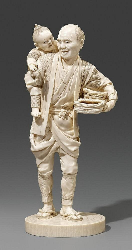 An ivory okimono of a peasant standing on a plain base and carrying a boy with a toad in his hand, the peasant holding two vegetable baskets with a knife inside. Signed Shuntei. Late 19th century