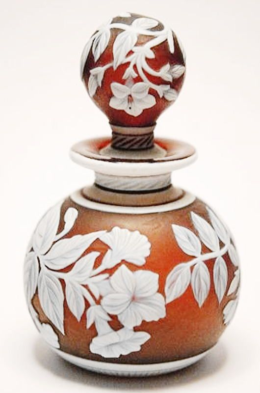 A late 19th Century Stourbridge glass cameo scent bottle, possibly Thomas Webb & Sons, of spherical form with a collar neck and spherical stopper, cased in opal over deep cinnamon and cut back with flowering boughs between
