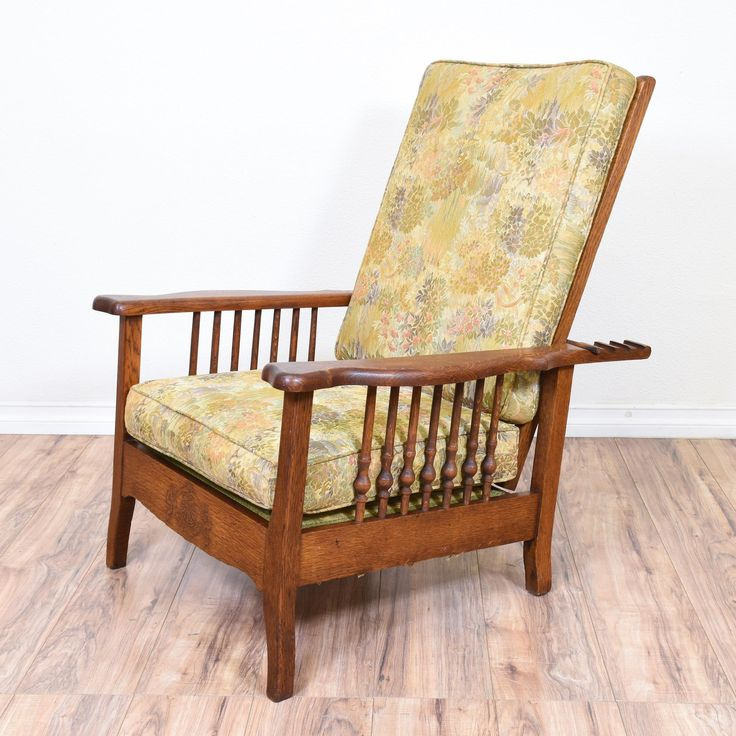 This Morris style recliner chair is featured in a solid wood with a glossy rustic oak finish. This craftsman style armchair has a tall reeling back, carved spindle sides and green floral upholstered cushions. Perfect for lounging in style! #countryfarmhouse #chairs #recliner #sandiegovintage #vintagefurniture
