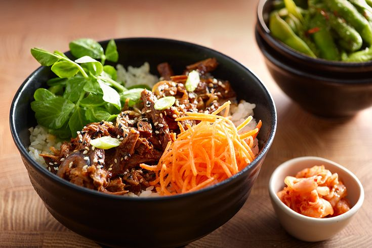 DONBURI. Beef brisket in teriyaki sauce with sticky white rice, shredded carrots, pea shoots and onions. Garnished with sesame seeds and served with a side of kimchee.
