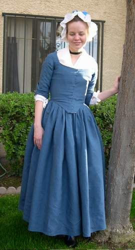 18th century round gown, over petticoats, with mob cap.