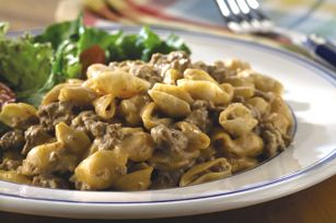 1lb. ground beef  2-1/2cups milk  1/4cup ketchup  2 Tbsp. yellow mustard  1 Tbsp. onion powder  1pkg. (12 oz.) VELVEETA Shells & Cheese Dinner  1/4cup BREAKSTONE'S or KNUDSEN Sour Cream  1 cup  chopped tomatoes (about 1 large)  1/4cup  sliced green onions