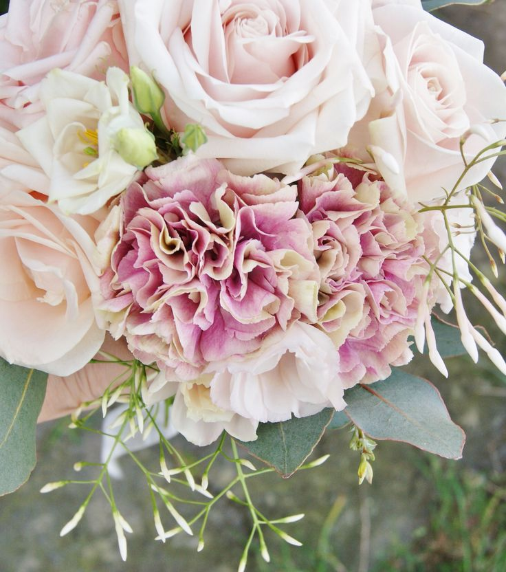 Pretty and romantic hand-tied bridal bouquet of pink sweet avalanche roses, trailing jasmine, lisianthus and gorgeous ruffled antigua carnation. Florissimo, Shropshire