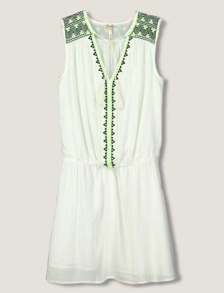 Robe fluide, coloris écru, broderies ethniques sur épaules et avec coloris noir et fluo. Col tunisien avec liens à nouer et pompons. Taille resserée. Doublure intérieure.Une robe idéale pour cet été.