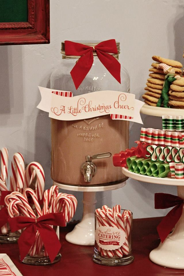 Glass dispenser filled with hot cocoa, green and red table scape using cake stands and candy canes/ribbon.