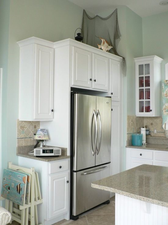 Refrigerator tucked away with storage above it and next to it thanks to a well-placed pantry cabinet!