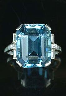 An art deco aquamarine dress ring, circa 1935, the rectangular step-cut aquamarine, to a claw mount and pierced gallery with channel-set baguette-cut diamond shoulders, finger size Q