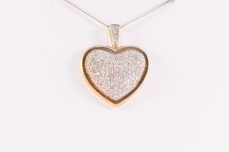 Beautiful and very large 9ct gold heart pendant, the middle section full of diamond clusterssurrounded by a yellow gold band encasing the diamonds. This is a very impressive piece. Pendant comes complete with a 20-inch 9ct white gold chain.