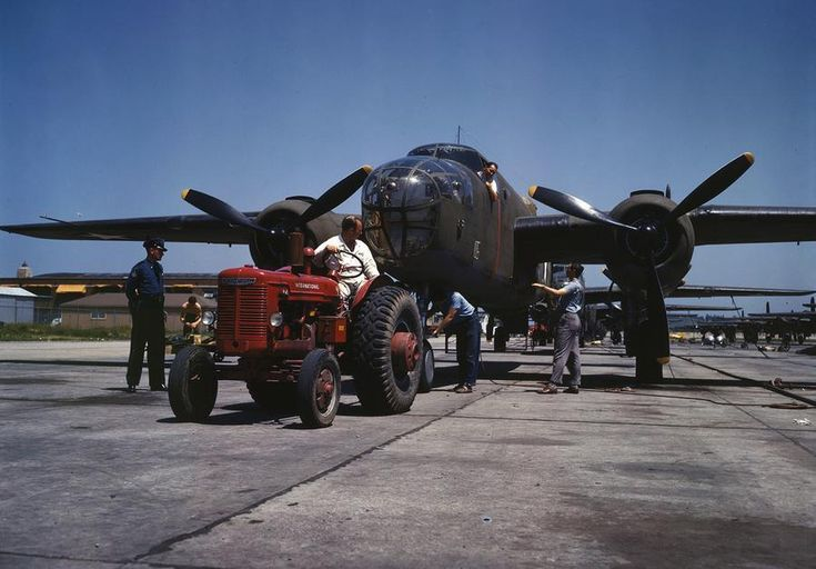 """B-25 bomber planes at the North American Aviation, Inc., being hauled along an outdoor assembly line with an """"International"""" tractor, in Kansas City, Kansas, in October, 1942."""