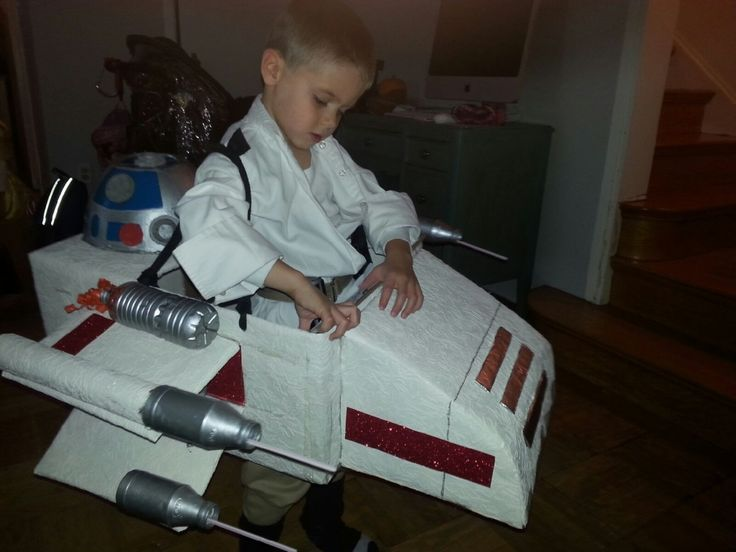 Luke Skywalker flying his X-Wing. Items used: used cardboard boxes, water bottles, yogurt drink bottles, old CDs, pie pans, ribbon and wall paper. Hot glue gun helped to stick it all together.