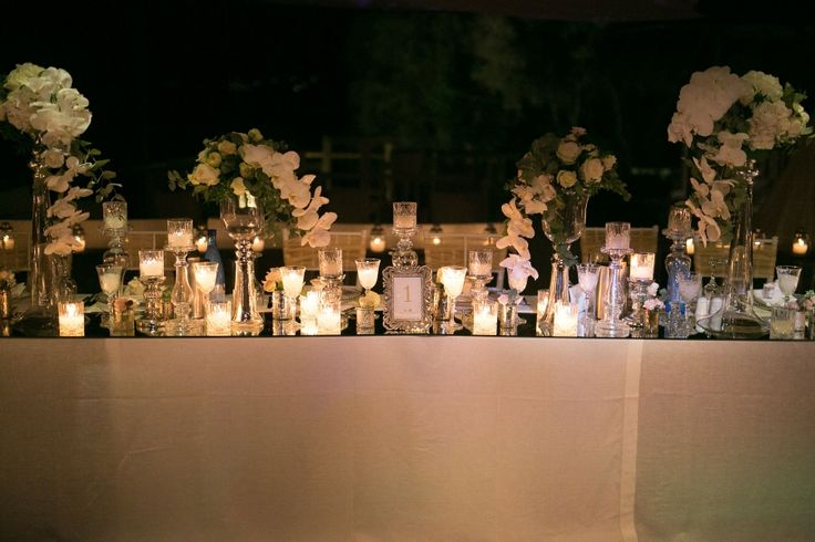 Mirros placed instead of runners, high flower compositions with hanging white orchids and o' hara roses and loads of candles make our table set up on this luxurious wedding!