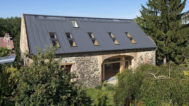 Moderní dřevostavba rodinného domu je vsazena do původního pláště historické stodoly