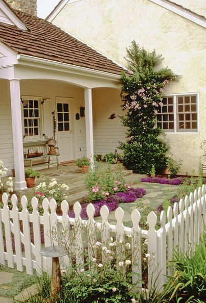 little fenced off part of the yard. Cottage style courtyard garden with white picket fence.