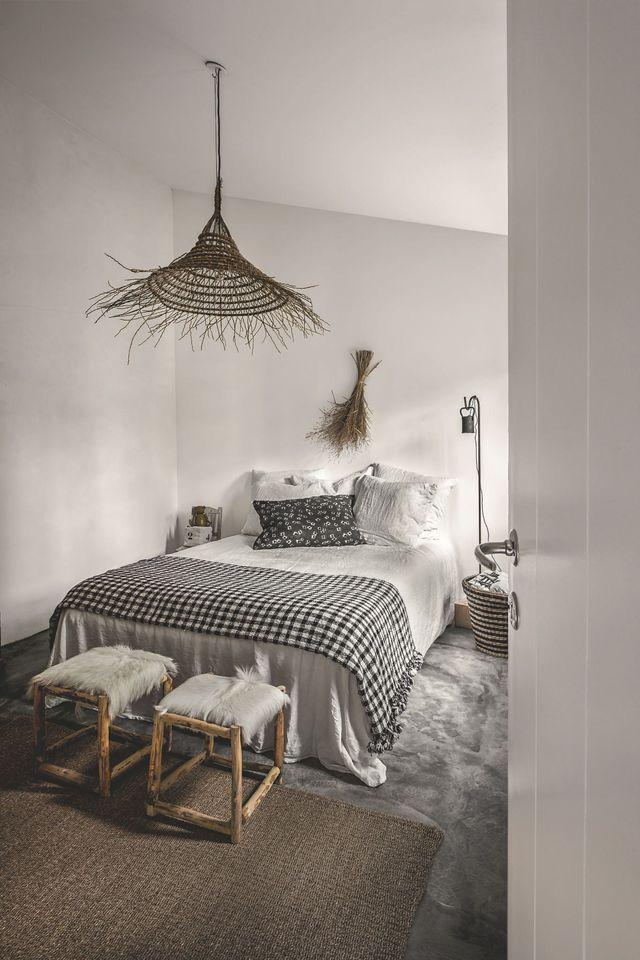Sur un sol gris en béton lissé, toute la fraîcheur d'un lit Ecume. Coussin à motif, Khadi and Co. Lustre en paille, tabourets et plaid, Rock the Kabah. Lampe de chevet, Les Petites Emplettes, corbeille en osier, Ikea.