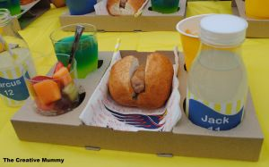 Take away coffee trays with a jelly cup, fruit salad, hot chips, hotdog and drink