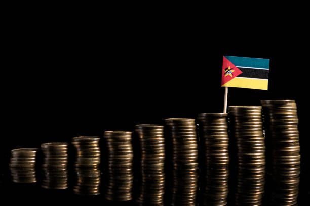 mozambique flag with lot of coins isolated on black background