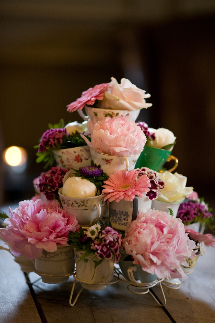 Beautiful vintage antique cake stand is adorned with delicate individual flowers and arrangements. Using vintage tea cups as miniature vases held in truly gorgeous cake stand.Inspirational flower design created for a truly creative bride as an imaginative centre piece. Love it!