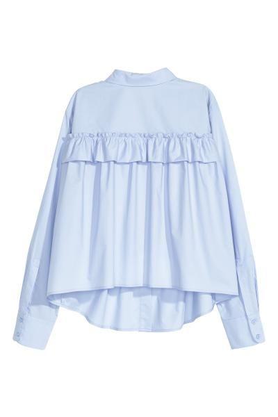 Blusa larga com folho: Blusa larga, de mangas compridas, em popelina de algodão com folho decorativo nas costas. Tem um bolso no peito, botões na frente e base ligeiramente arredondada.