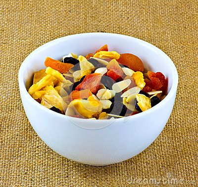 A closeup dried tropical fruit with almonds in a bowl