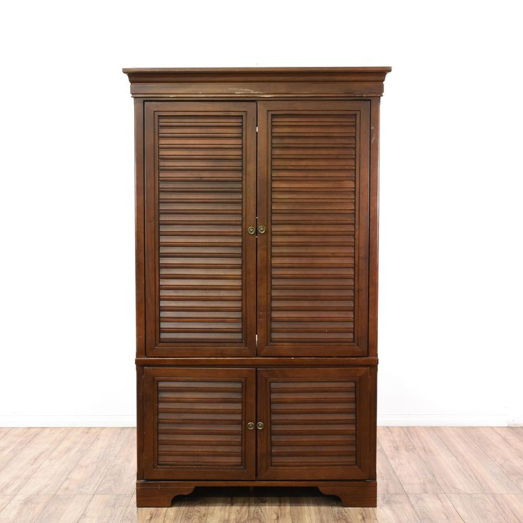 This armoire is featured in a solid wood with a mahogany stain. This traditional style wardrobe has shutter front doors, a bottom cabinet with interior shelving, sliding shelves, and ample closet space. Perfect for organizing clothing and shoes! #americantraditional #dressers #armoireorwardrobe #sandiegovintage #vintagefurniture
