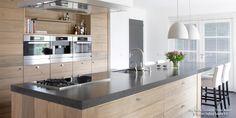 Groot eikenhouten kookeiland met granieten werkblad toont de mogelijkheden van een op maat gemaakte keuken.