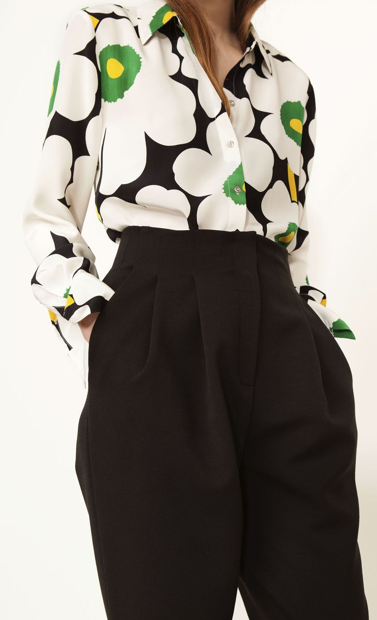 This blouse is made of lightweight silk in the classic Unikko print. It has a straight cut to the hip hemline that's slightly curved and longer in the back. The front closure and cuffs secure with small metal buttons.