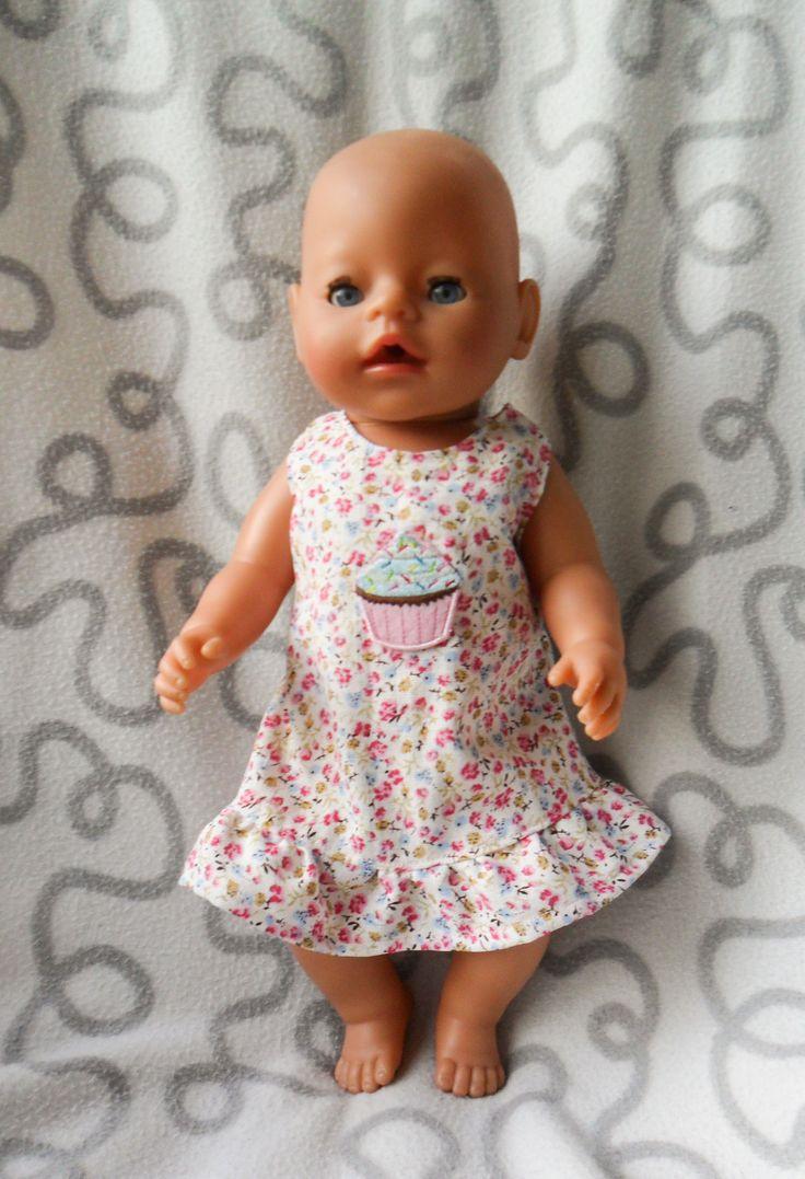 Met deze halterjurk is de 43 cm babypop helemaal klaar voor de zomer. De jurk sluit met strikbandjes in de nek en heeft elastiek in de taille achter. Hij is makkelijk aan en uit te trekken. De  jurk past over een badpak of bikini