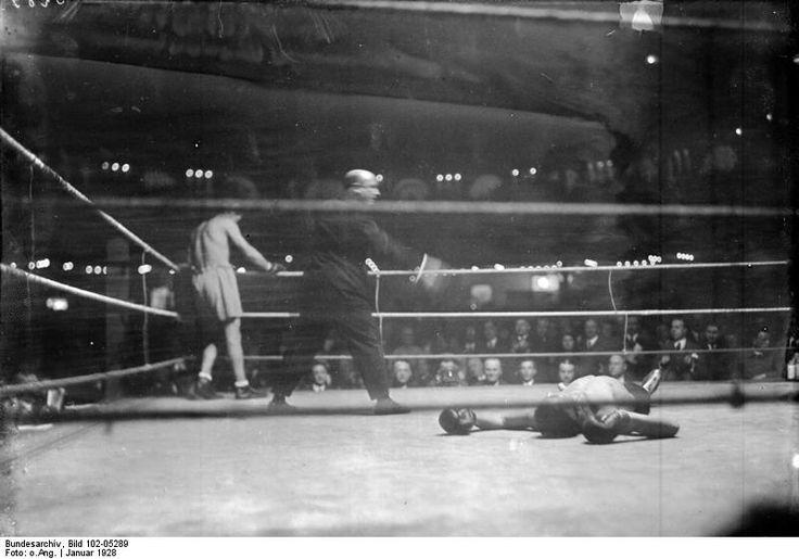 1928 Berlin Sportpalast Der deutsche Box-Europa-Halbschwergewichtsmeister Max Schmeling (links) schlägt den italienischen Meister Bonaglia vor Zehntausenden von Zuschauern in der ersten Runde k.o. . Momentaufnahme des Niederschlages. Der Ringrichter zählt den am Boden liegenden Italiener Bonaglia aus.