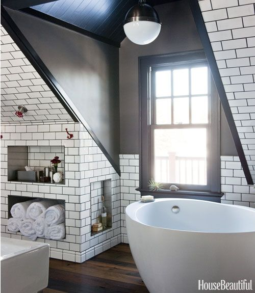 The .25 tub by Waterworks adds curves to a bathroom dominated by angles. Ruhland tiled wainscoting and eaves, using a dark gray grout for a more graphic effect. Walls are painted Kendall Charcoal and trim is Black Tar, both by Benjamin Moore.  I LOVE THIS BATHROOM