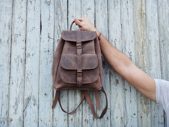 This classic unisex small size backpack/rucksack is handmade with Greek full grain cowhide leather in its brown color and has no lining. It features a main section that closes with a drawstring closure and a fold-over flap with a metal buckled strap. With an additional pocket on the front zipped pocket on the back, for quick access, this fair sized rugged and yet elegant bag is adorned with stitched detail.  DIMENSIONS:  Small Size: Height: 11.81 / 30 cm Width: 10.24 / 26 cm Depth: 3.94…
