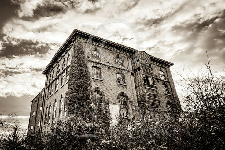 Rundown building in the heart of town...  Old mill in black and white with a moody sky, undergrowth growing around it with ivy creeping up the side.