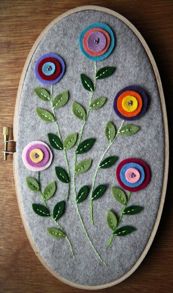 Felt flowers in an oval hoop: I like the circle flowers and think they could be appliquéd with cotton fabric on a quilt