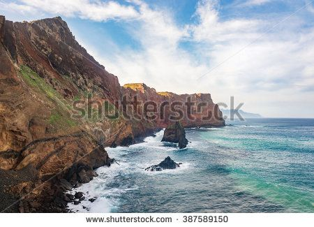 Picturesque colorful geological cliffs located on eastern part of Madeira coastline with rocky desert fields, generic plants and unique lava stone beaches.