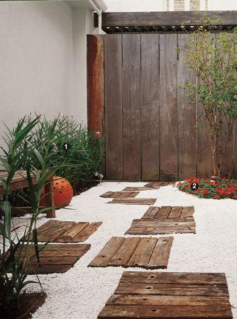 Caminho em área externa em placas com madeira de cruzetas de demolição e pedriscos brancos.