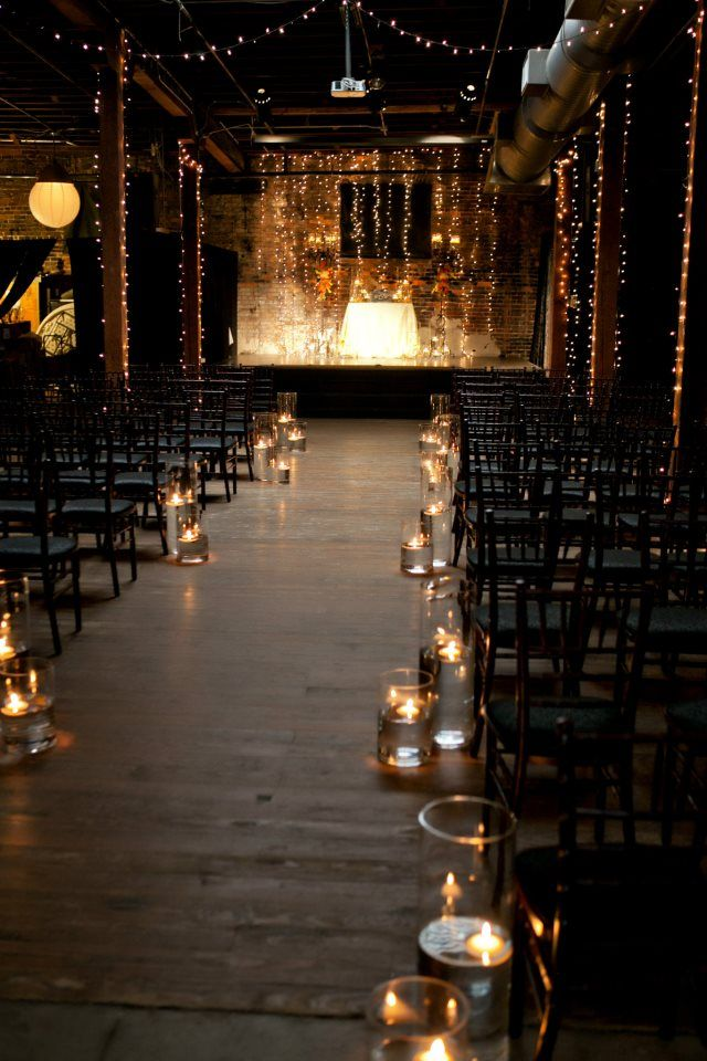 Ceremony set up in a beautiful old warehouse with romantic lighting. photo…